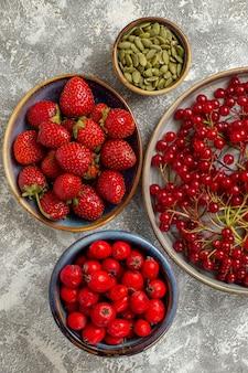 Vista de cima cranberries vermelhas frescas com outras frutas em fundo branco claro
