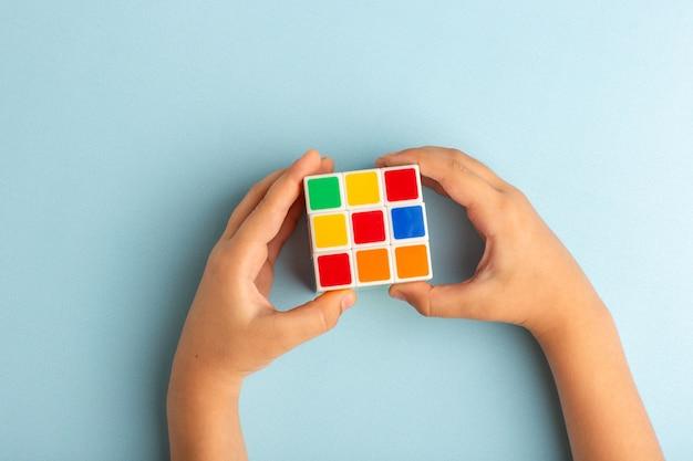 Vista de cima, criança brincando com o cubo de rubis na mesa azul gelo