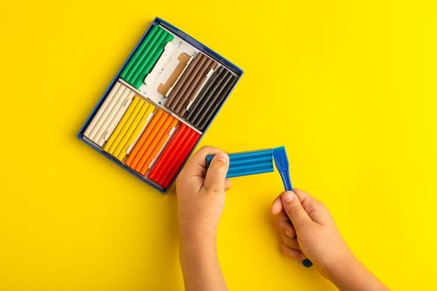 Vista de cima, criança de plasticinas coloridas trabalhando e brincando com ela na foto de cor amarela da escola infantil