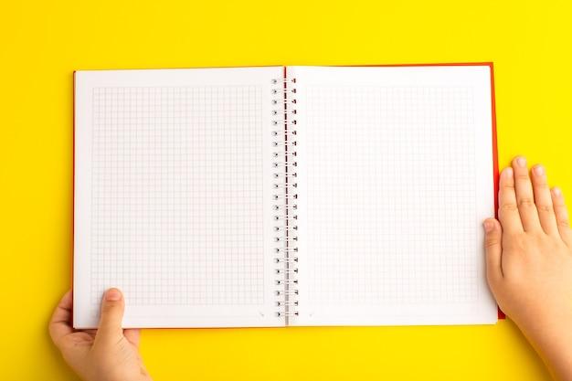 Vista de cima, criança segurando o caderno na mesa amarela