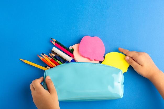 Vista de cima, criança segurando uma caixa de caneta azul cheia de lápis coloridos na superfície azul