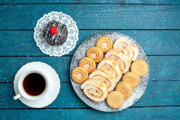 Vista de cima da bola de chocolate gostoso com uma xícara de chá e biscoitos na mesa rústica azul chá bolo doce biscoito