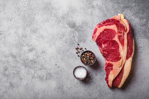 Vista de cima da carne crua, suculenta, em mármore, filé de costela pronta para cozinhar, com temperos, fundo rústico de concreto cinza, espaço para texto