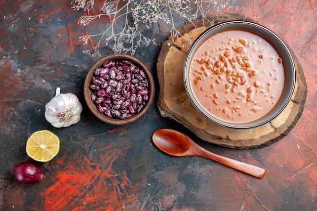 Vista de cima da clássica sopa de tomate em uma tigela azul na bandeja de madeira, garrafa de óleo, feijão, alho, cebola e limão, na mesa de cores misturadas