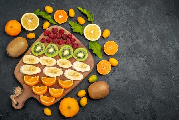 Vista de cima da coleção de frutas frescas picadas em uma tábua de madeira ao redor dela na mesa preta