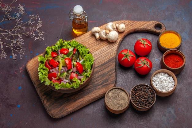 Vista de cima da comida no tabuleiro, salada com tomate, pimentão verde, óleo de alface e temperos diferentes
