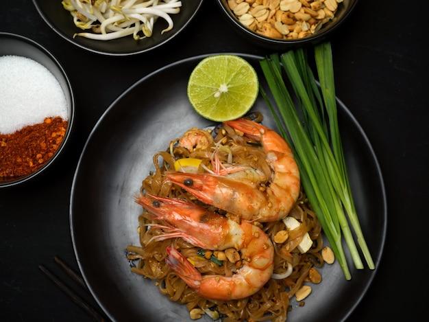 Vista de cima da comida tailandesa, macarrão tailandês refogado com camarão servindo com limão, broto de feijão e cebolinha, pad thai