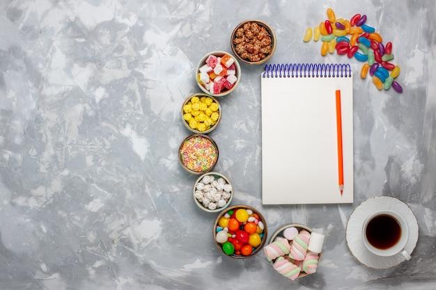 Vista de cima da composição de doces de diferentes cores, com bloco de notas de marshmallow e chá na mesa branca.