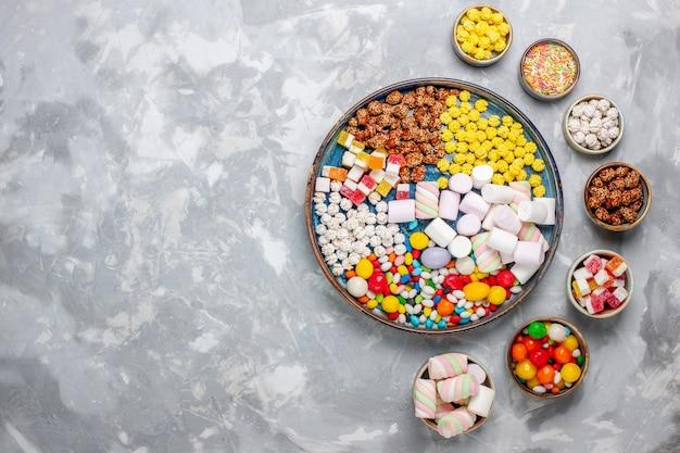 Vista de cima da composição de doces, doces de cores diferentes com marshmallow na mesa branca-clara.