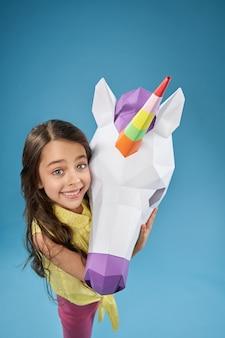 Vista de cima da criança feliz, mantendo o unicórnio de papel