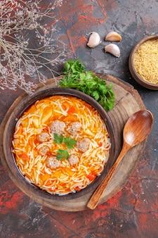 Vista de cima da deliciosa sopa de macarrão com frango na tábua de madeira, verduras, colher de alho no fundo escuro