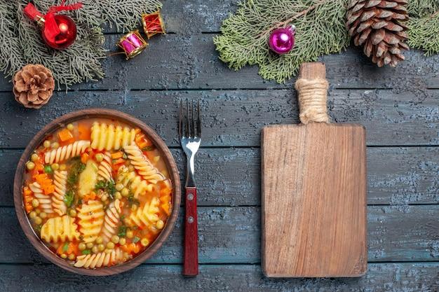 Vista de cima da deliciosa sopa de massa de macarrão espiral italiano com verduras em azul-escuro cozinha de mesa prato de massa colorida jantar
