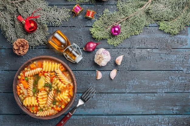 Vista de cima da deliciosa sopa de massa de macarrão espiral italiano com verduras na mesa azul-escura cozinha sopa de massa prato de jantar cor