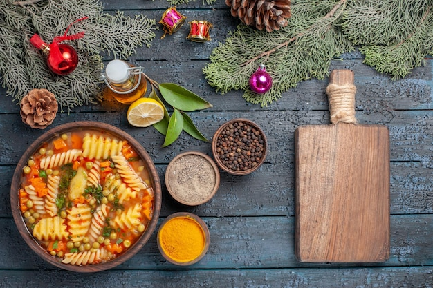 Vista de cima da deliciosa sopa de massa de macarrão espiral italiano com verduras na mesa azul-escuro cozinha sopa de massa prato de jantar cor
