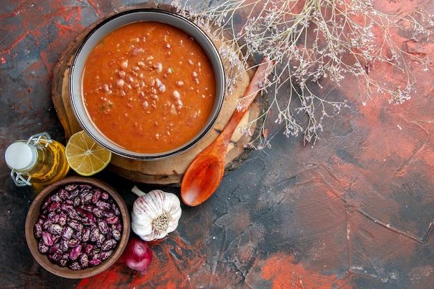 Vista de cima da deliciosa sopa para o jantar com uma colher e limão em uma bandeja de madeira, feijão, cebola, alho, garrafa de óleo, mesa de cores misturadas