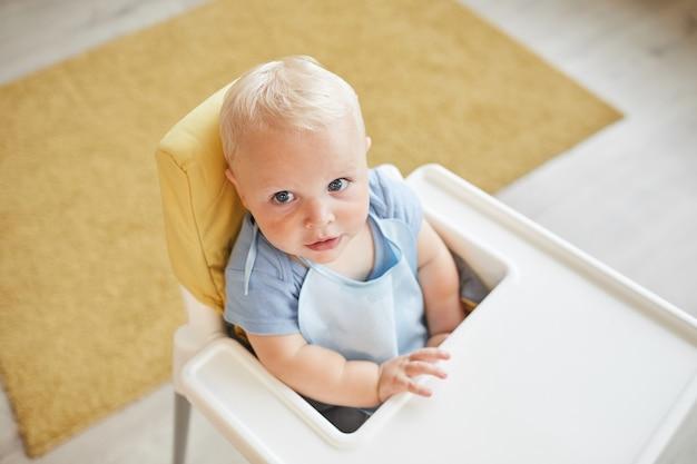 Vista de cima da foto de uma criança pequena usando babador sentado na cadeira alta esperando a refeição