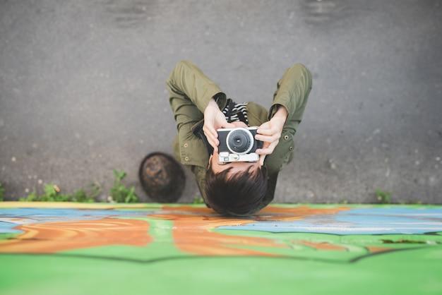 Vista de cima da jovem e bela mulher caucasiana marrom curto segurando uma câmera instantânea