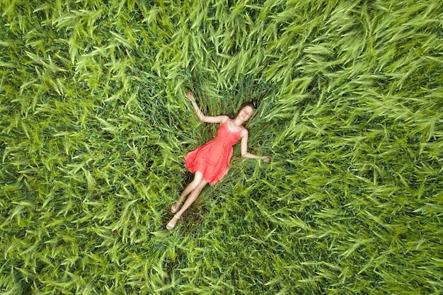 Vista de cima da jovem mulher magro atraente vestido vermelho deitado com os olhos fechados no campo de trigo verde.