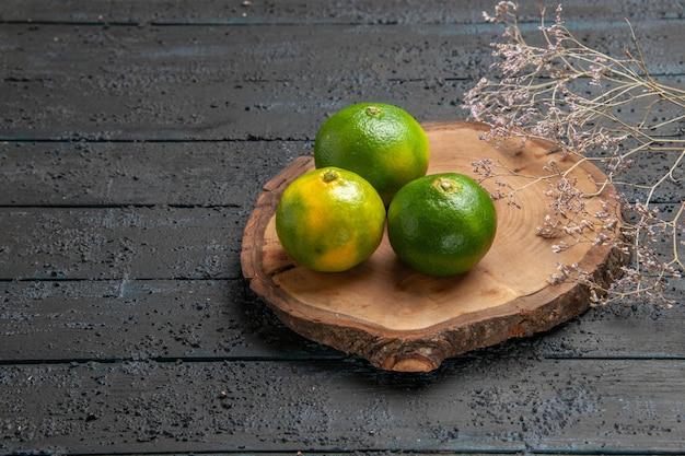 Vista de cima da lima na mesa, limas na placa de madeira marrom no centro da mesa cinza ao lado dos galhos
