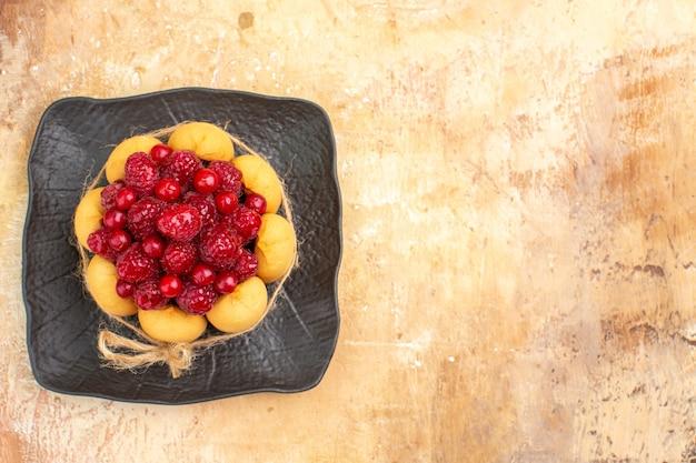 Vista de cima da mesa posta para o café e a hora do chá com framboesas em bolos na mesa de cores misturadas