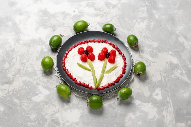 Vista de cima da metade de grânulos de romã fresca com feijoas no espaço em branco