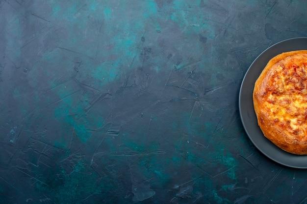 Vista de cima da pizza assada com queijo na mesa azul-escura