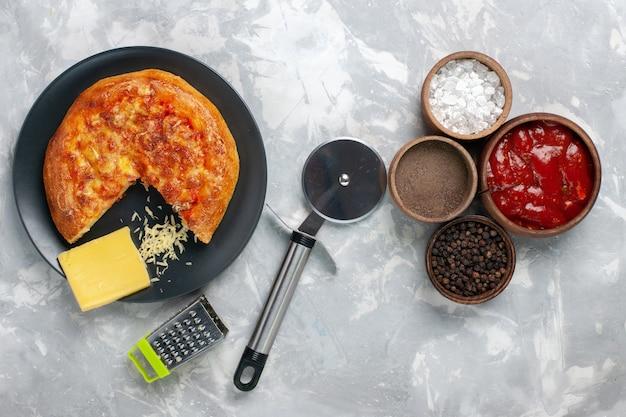 Vista de cima da pizza assada com temperos diferentes em mesa branca
