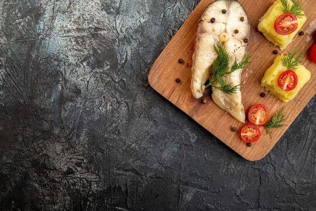 Vista de cima da refeição de trigo sarraceno de peixe cozido servido com tomate verde e queijo em uma tábua de madeira na superfície do gelo