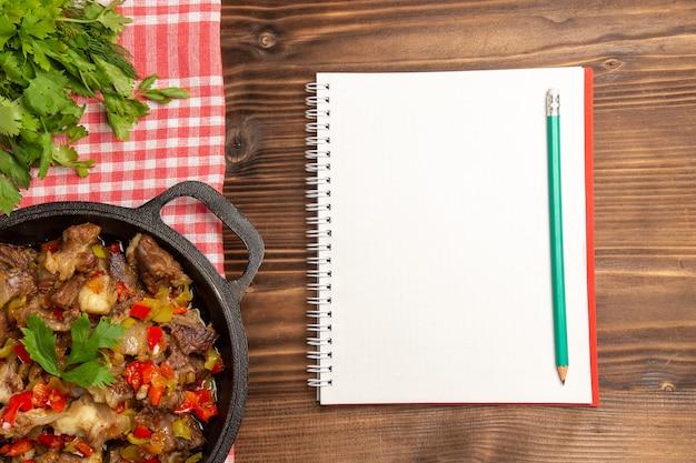 Vista de cima da refeição de vegetais cozidos, incluindo vegetais e carne dentro de uma mesa marrom