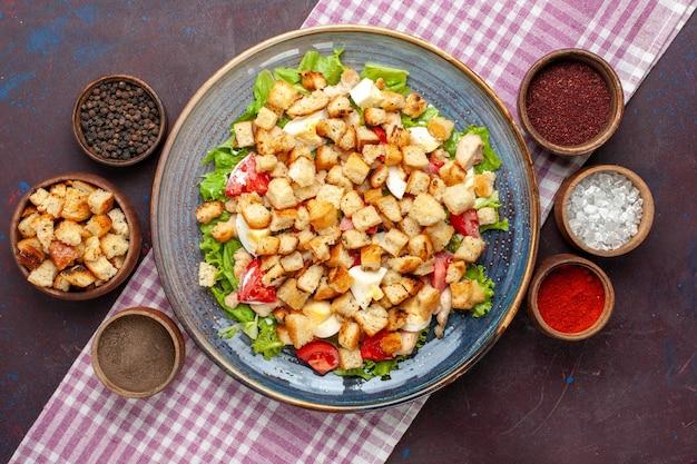 Vista de cima da saborosa salada caesar com bolachas e temperos na mesa escura