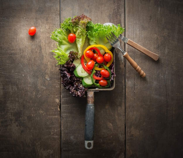 Vista de cima da salada com tomates de cereja na tabela de madeira