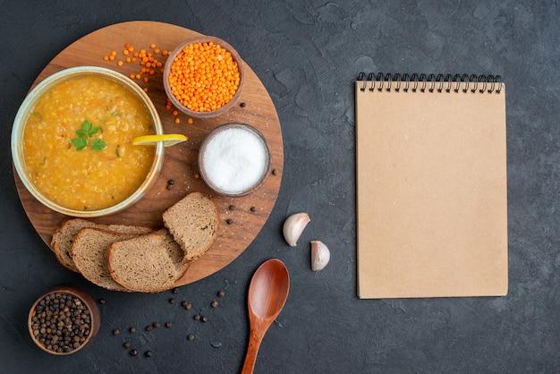 Vista de cima da sopa de lentilhas com lentilhas crus salgadas e pães escuros na superfície escura