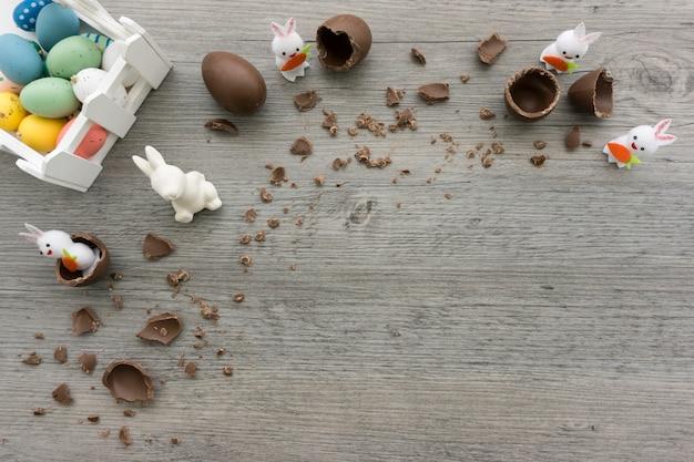Vista de cima da superfície de madeira com ovos de páscoa e coelhos