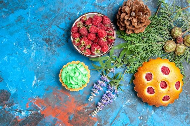 Vista de cima da tigela de framboesa pequena torta de bolo de baga galhos de pinhas na superfície azul