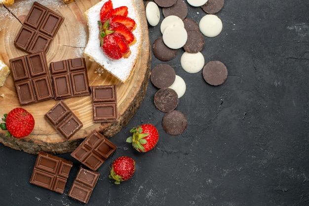 Vista de cima das fatias de bolo com biscoitos e barras de chocolate em um fundo escuro