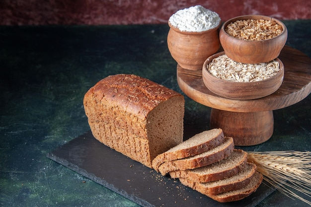 Vista de cima das fatias de pão preto, farinha de trigo sarraceno de aveia em uma placa de cor escura em um fundo de cor mista