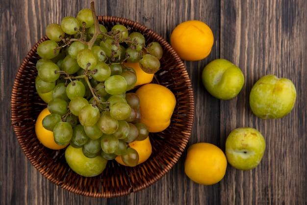 Vista de cima das frutas como pluota verde uva e nectacotes na cesta e padrão de pluots e nectacots no fundo de madeira