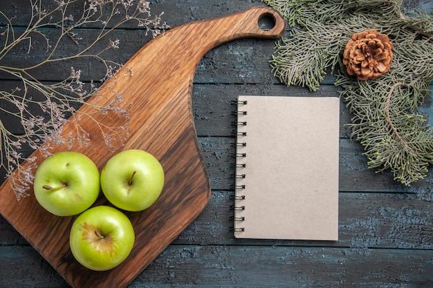 Vista de cima das maçãs do topo a bordo de três maçãs verdes na mesa da cozinha e um caderno entre galhos de árvores com cones na mesa escura