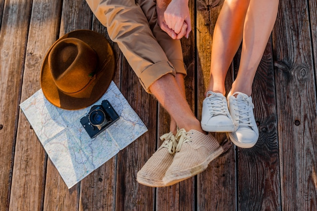 Vista de cima das pernas de um casal viajando no verão usando tênis