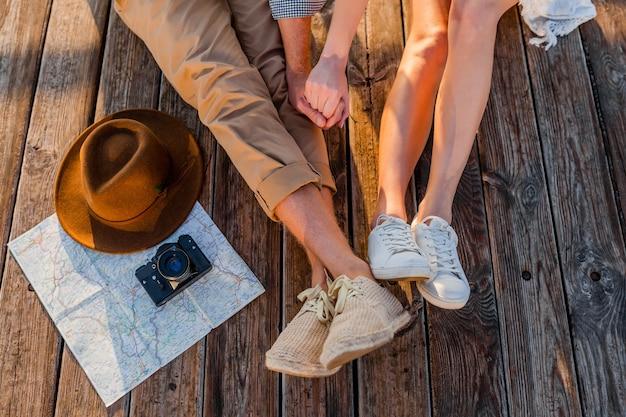Vista de cima das pernas de um casal viajando no verão vestido com tênis, moda estilo boho hipster de homem e mulher se divertindo juntos, mapa, chapéu, câmera fotográfica, passeios turísticos, moda de calçados