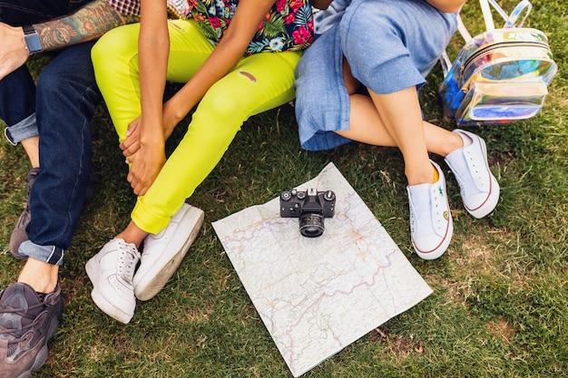 Vista de cima das pernas e sapatos de uma jovem companhia de amigos sentados no parque, homens e mulheres se divertindo juntos