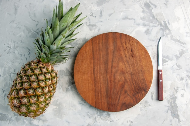 Vista de cima de abacaxi dourado fresco inteiro e faca de tábua de corte na mesa na superfície de mármore