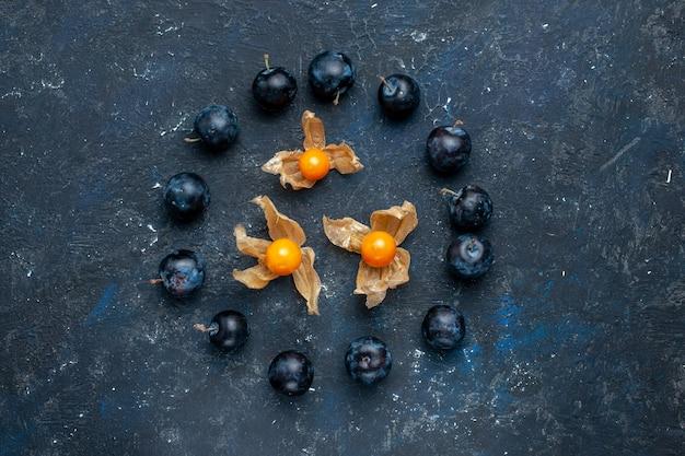 Vista de cima de abrunheiros frescos alinhados em círculo na mesa escura, vitamina de frutas frescas e vitaminas