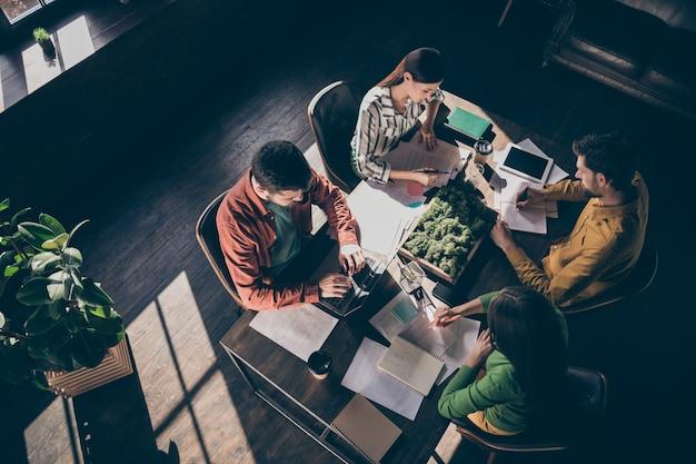 Vista de cima, de alto ângulo, de quatro empresários profissionais ocupados usando papéis de carta em trajes formais casuais
