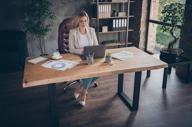 Vista de cima, de alto ângulo, mulher inteligente e focada, calculando o salário de funcionários de sua empresa com sapatos de salto alto