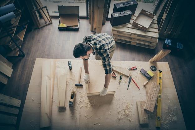 Vista de cima, de alto ângulo, pensativo artesão pensativo fazendo moldura com blocos de madeira cercados por instrumentos