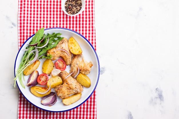 Vista de cima de asas de frango com batatas