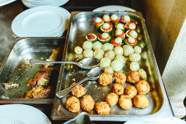 Vista de cima de bandeja de catering com batatas e medalhões de carne.