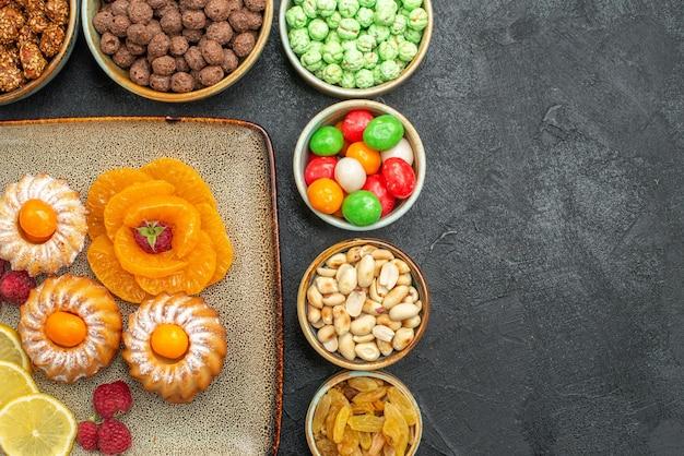 Vista de cima de bolinhos gostosos com doces, frutas e nozes em cinza