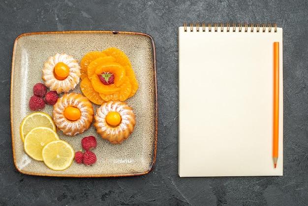 Vista de cima de bolinhos gostosos com fatias de limão e tangerinas em cinza